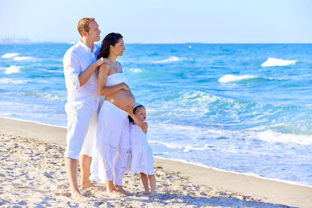 enceinte: Happy family on the beach posing relaxed with pregnant mother woman Stock Photo