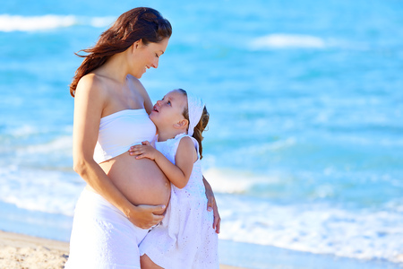 enceinte: Pregnant mother and daughter on the beach together hug Stock Photo