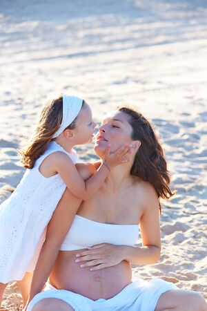 Pregnant mother and daughter on the beach together hug sitting on sand photo