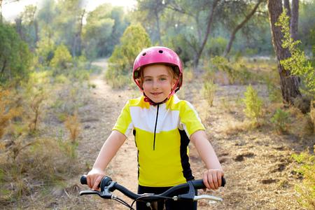 mediterranean forest: kid girl biker in mountain bike MTB at mediterranean forest Stock Photo
