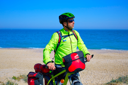 saddlebag: cycling tourist MTB cyclist in Mediterranean beach with paniers and saddlebag