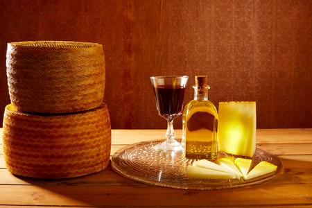 aceite de oliva: Queso manchego de España con aceite de oliva y vino tinto en la madera Foto de archivo