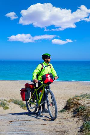 saddlebag: MTB Biker Bicycle touring on a beach with pannier racks and saddlebag Stock Photo