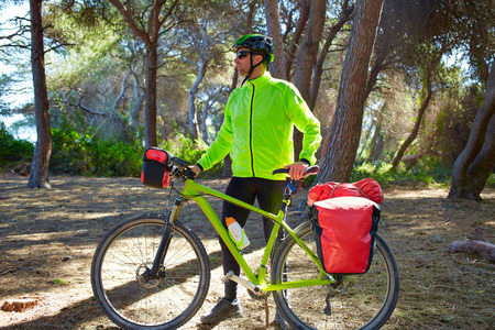 touring: MTB Biker Bicycle touring in a pine forest with pannier racks and saddlebag