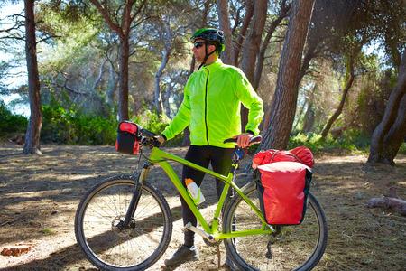 saddlebag: MTB Biker Bicycle touring in a pine forest with pannier racks and saddlebag