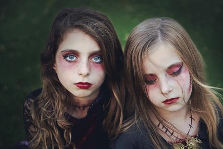Halloween makeup kid sister girls blue eyes in outdoor backyard lawn Stock Photo