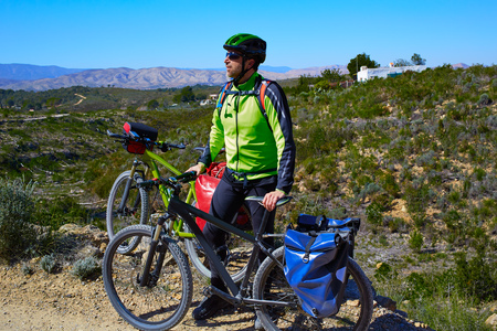 saddlebag: cycling tourist MTB cyclist in Pedralba Valencia with paniers and saddlebag Spain