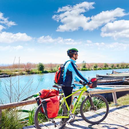 saddlebag: MTB Biker Bicycle touring on the river with pannier racks and saddlebag