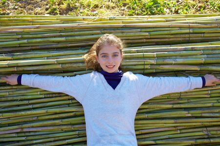 harmless: Kid girl relaxed in green canes background in autumn winter Stock Photo