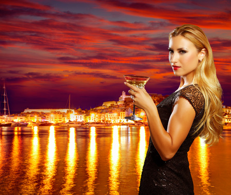 elegant party: Blond tourist girl drinking vermout cup at Ibiza nightlife sunset photomount Stock Photo