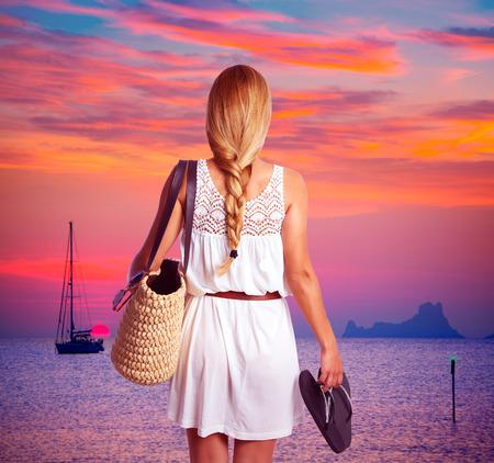 mujeres de espalda: Muchacha turística trenza rubia que mira puesta de sol con flip flop en la playa de Formentera photomount Foto de archivo