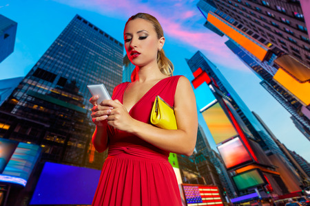 red telephone: Blond girl red dress smartphone chat writing in Times Square of New York Photomount Stock Photo