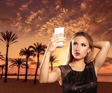beach sunset: Blond tourist girl taking selfie photo Mallorca Arenal beach sunset photomount