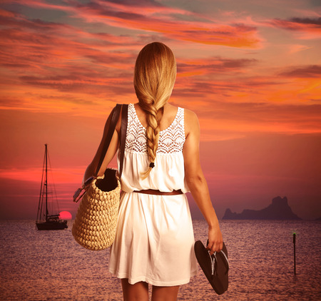 ibiza: Blond braid tourist girl looking sunset holding flip flop in beach of Formentera photomount