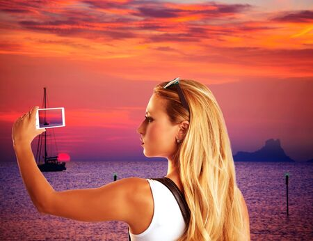 vedra: Blond tourist taking photograph sunset with smartphone in Formentera photomount