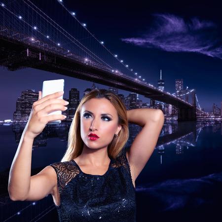 mujeres elegantes: Rubio turística foto autofoto en Brooklyn puente de la noche photomount Foto de archivo