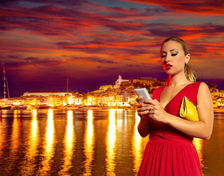 red telephone: Blond tourist girl smartphone chat in Ibiza nightlife sunset photomount Stock Photo