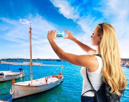 colom: Blond tourist in Mallorca taking photos of Porto Colom photomount Stock Photo