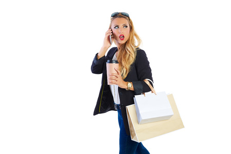 Blond shopaholic woman with bags talking with smartphone on white background photo