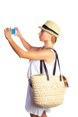 Blond tourist girl taking photos with smartphone white summer dress and basket bag photo
