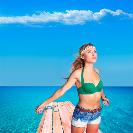 Blond sexy tourist girl in tropical beach pier of Formentera photomount photo