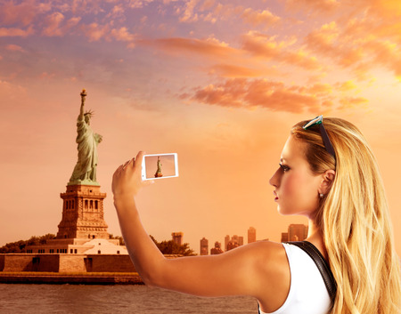 Blond tourist taking photo to Statue of Liberty in New York photomount photo