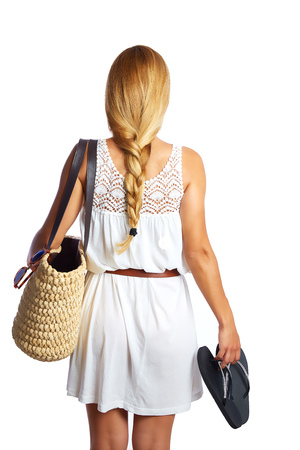 Blond tourist girl with flip flop shoes white summer dress and basket bag going beach rear view photo