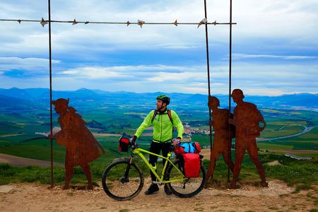 El Camino de Santiago Alto del Perdón superior con escultura de acero de peregrinos en Navarra con el motorista photo