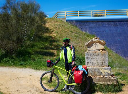 The way of saint James biker at stone sign Palencia Spain photo