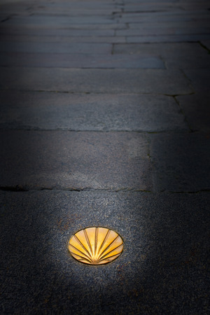 pilgrim journey: Santiago de Compostela end of Saint James Way golden shell sign on soil in Galicia Spain