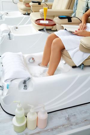 Pedicure feet bath in sofa chair woman at nails salon