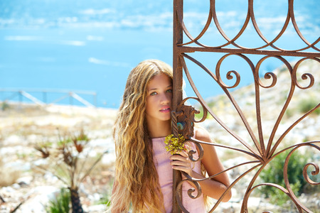 costa blanca: Blond girl in Mediterranean rusted gate with sea in background