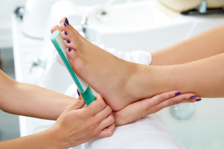 woman in towel: Pedicure dead skin remover foot rasp woman in nail salon