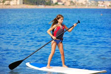 brunette girl: Kid paddle surf surfer girl with row in mediterranean beach