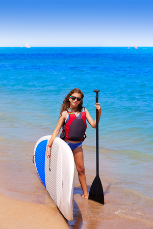 row: Kid paddle surf surfer girl with row in mediterranean beach