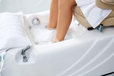 Pedicure voeten bad in fauteuil vrouw bij nagels salon