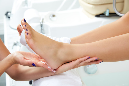 pedicure: Pedicure moisturizing cram after dead skin remover foot rasp woman in nail salon Stock Photo