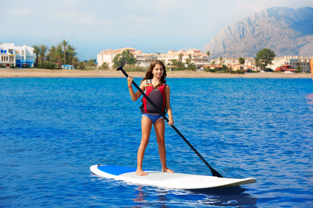 lifejacket: Kid paddle surf surfer girl with row in mediterranean beach