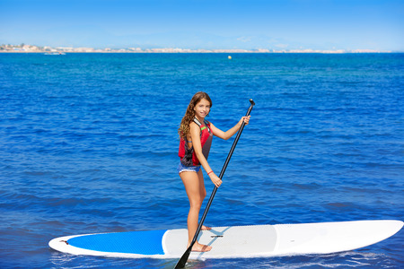 small girl: Kid paddle surf surfer girl with row in mediterranean beach