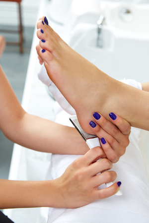 rasp: Pedicure dead skin remover foot rasp woman in nail salon
