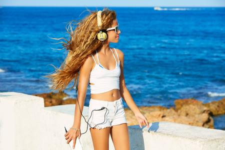 costa blanca: Blond kid teen girl hearing headphones music on smartphone in a beach Stock Photo