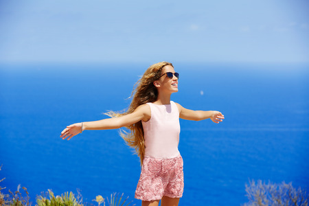 open air: Blond girl shaking hair on air at blue Mediterranean sea tourist in Spain open hands Stock Photo