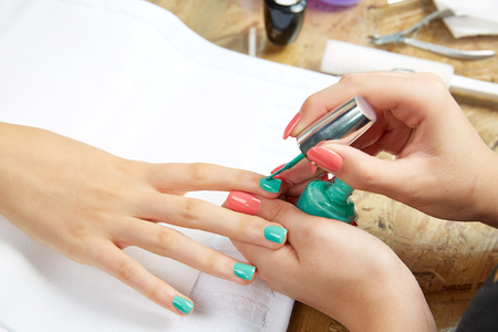 applying: Nails painting with brush in Nail Salon woman hands