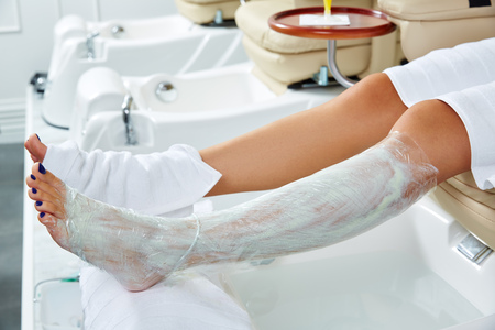 salon: Pedicure nourishing moisturizer mask legs cling film wrap heat effect in nail salon Stock Photo