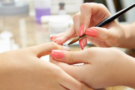 Nails peinture avec une brosse en Nail Salon mains de femme Banque d'images