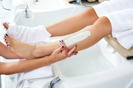 pedicura: Pedicura aplying máscara hidratante nutritiva en las piernas de la mujer en salón de uñas