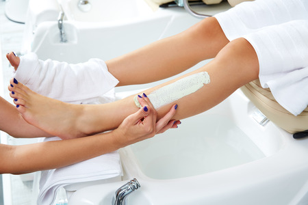 nourishing: Pedicure aplying nourishing moisturizer mask in legs of woman in nails salon