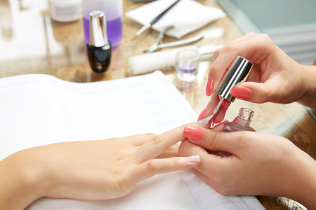 pink nail polish: Nails painting with brush in Nail Salon woman hands
