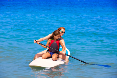 teaching: Kid paddle surf surfer girl with row in mediterranean beach