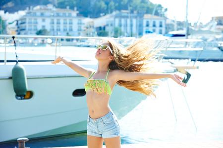 niñas bonitas: Muchacha adolescente rubia del cabrito en el puerto mediterráneo de España sacudiendo el pelo al viento Foto de archivo